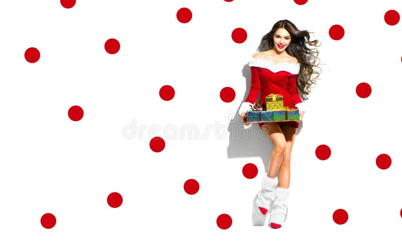 Christmas scene. Santa. Beauty model girl wearing red party costume royalty free stock images