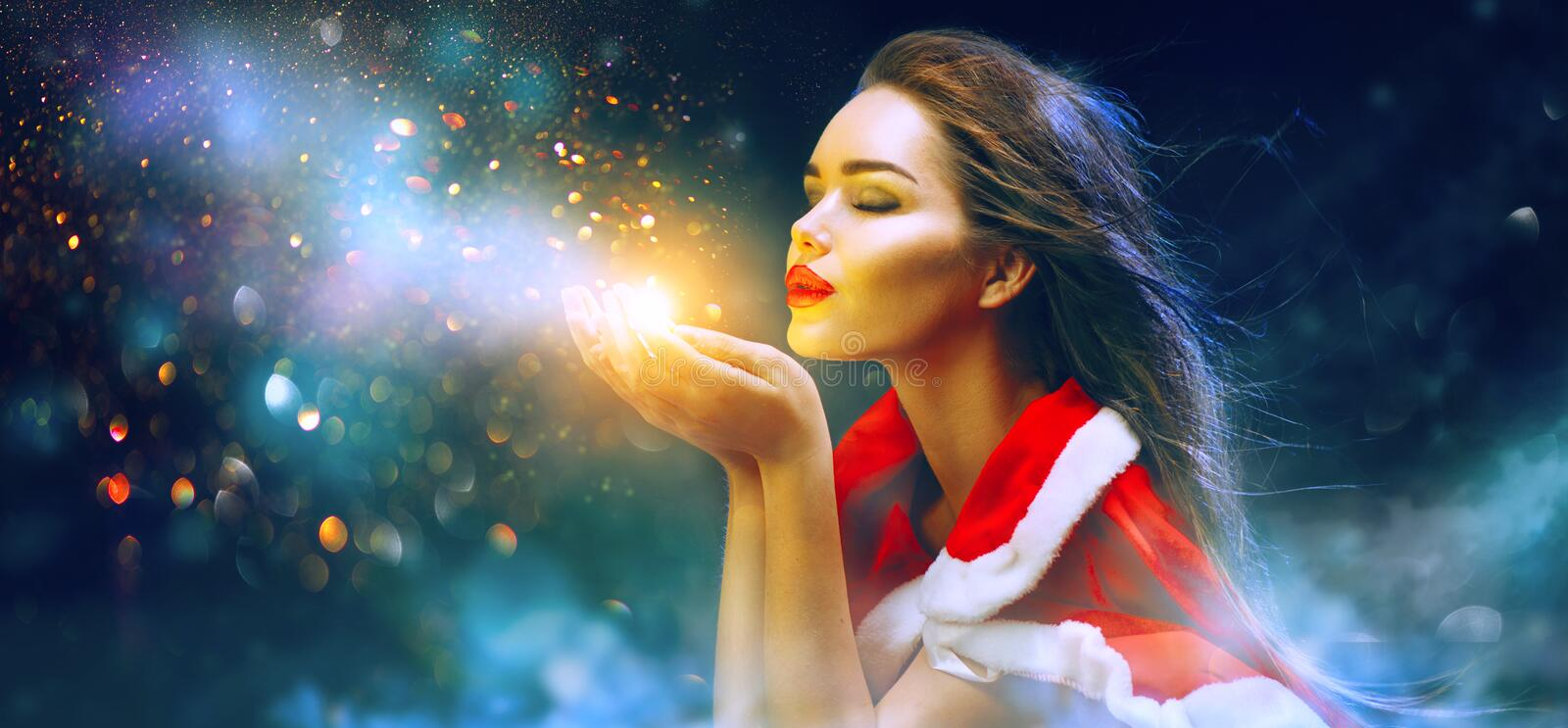 Christmas scene. Santa. Brunette young woman in party costume blowing snow stock image