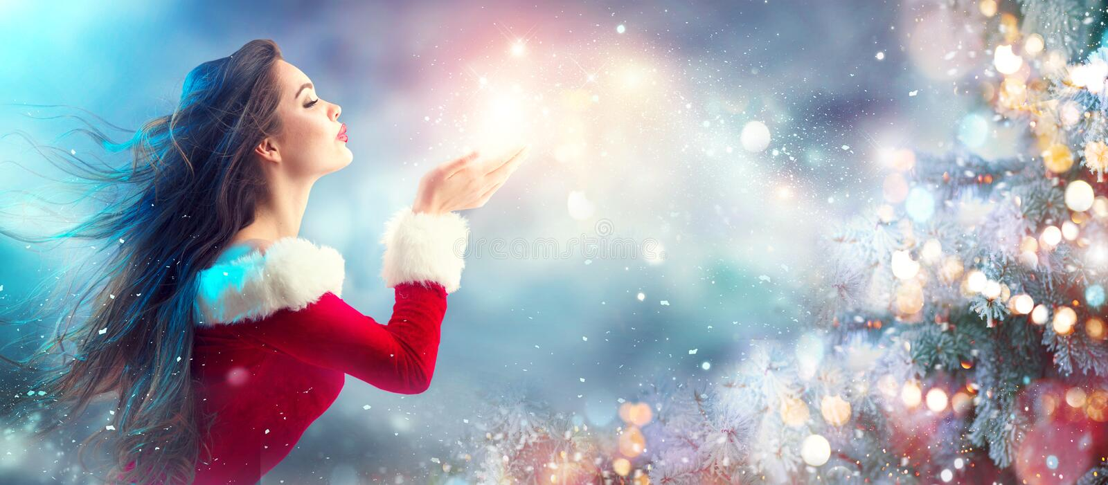 Christmas scene. Santa. Brunette young woman in party costume blowing snow. Over holiday blurred background stock image