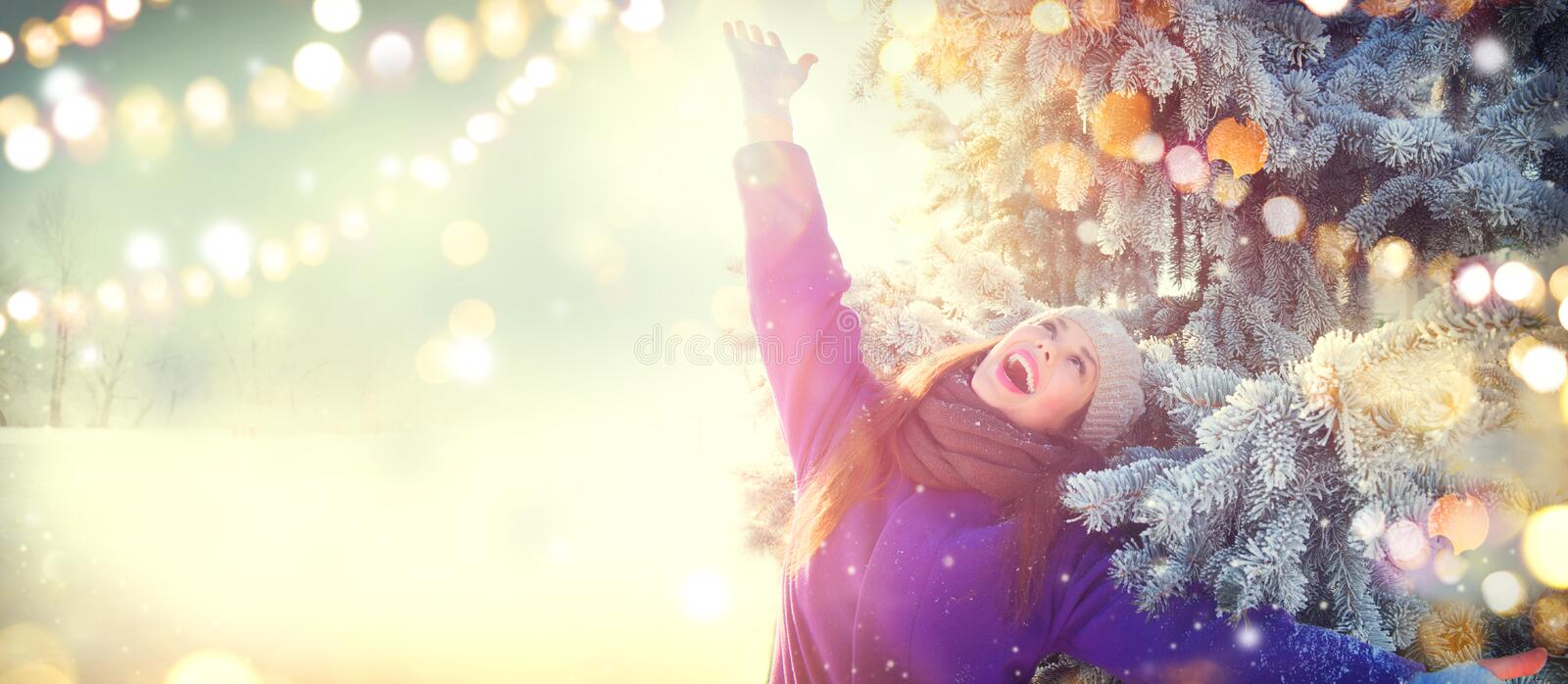 Christmas scene. Winter joyful beauty girl having fun outdoors in winter park under decorated Christmas tree royalty free stock photography