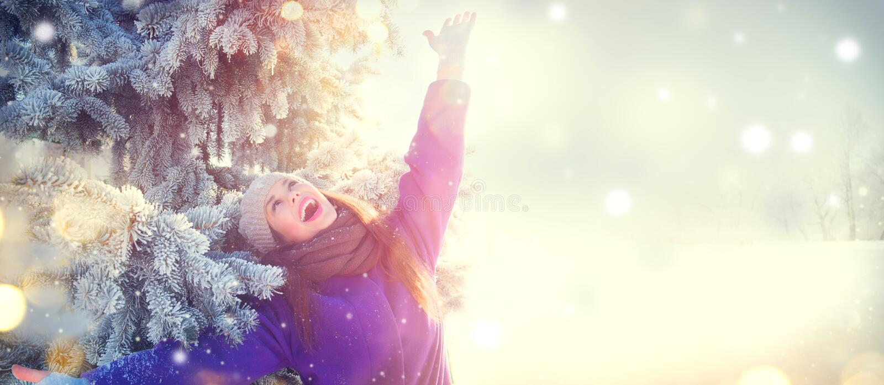 Christmas scene. Winter joyful beauty girl having fun outdoors in winter park under decorated Christmas tree stock photos