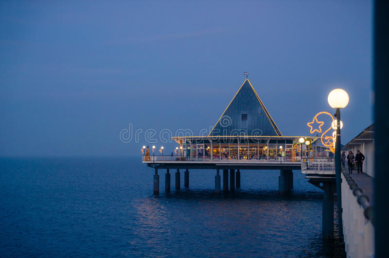 Christmas scenery pier architecture on sea-bridge. Beautiful christmas scenery panorama pier architecture on sea-bridge with decorated Xmas Tree in Christmas royalty free stock images