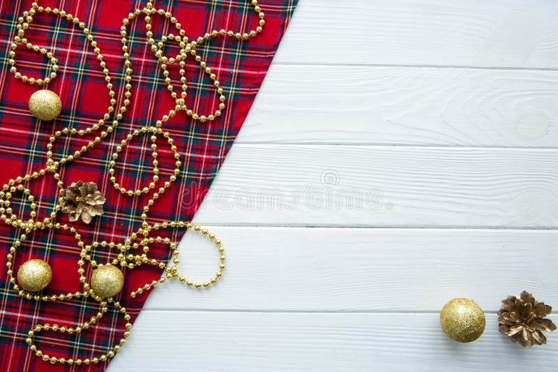Scotish Christmas background. Golden balls, pine cones and golden beads decorations. Space for text. Christmas scottish pattern fabric backgtound. Golden royalty free stock photo