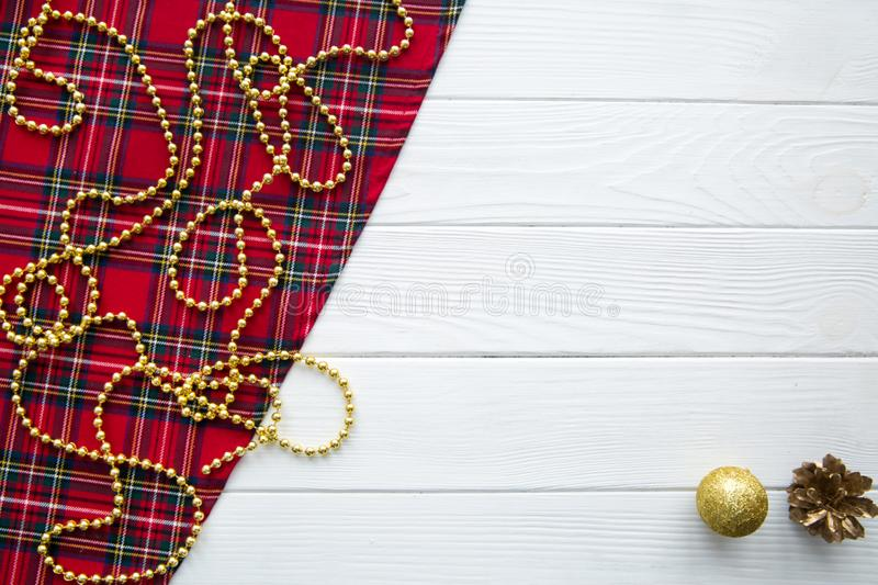 Scotish Christmas background. Golden balls, pine cones and golden beads decorations. Space for text. Christmas scottish pattern fabric backgtound. Golden royalty free stock photography