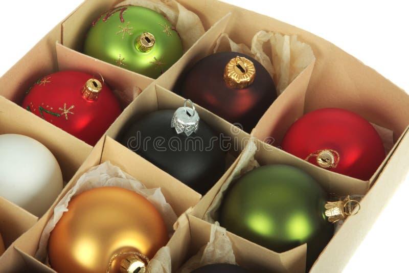 Christmas season. Old cardboardbox full of christmas ball ornaments, shot on white royalty free stock image