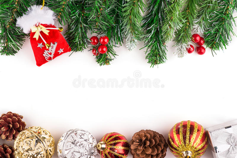Christmas seasonal border of holly, ivy, mistletoe, cedar leaf sprigs with pine cones and gold baubles. Over white background with copyspace. Christmas stock photo