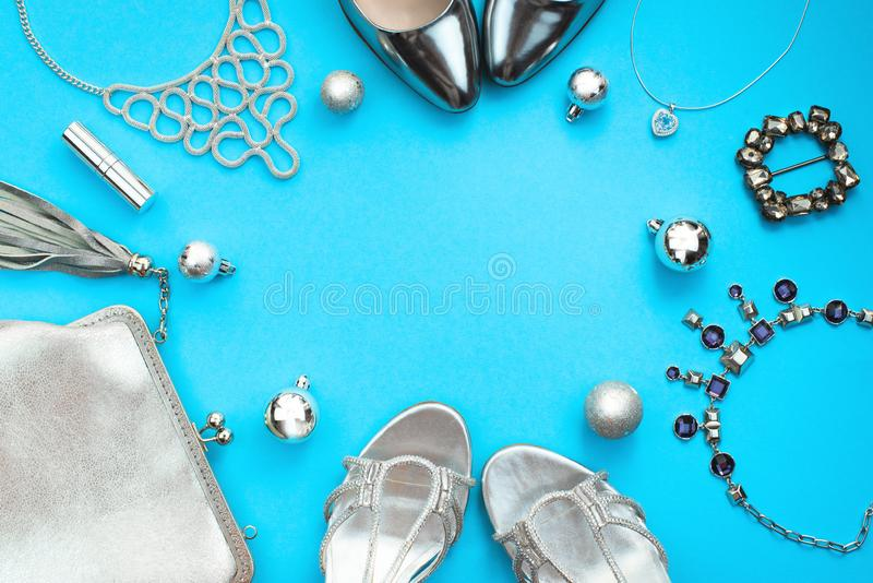 Christmas Set of fashion accessories flat lay shoes handbag necklace jewelry silver color on blue background Top view copy space royalty free stock images