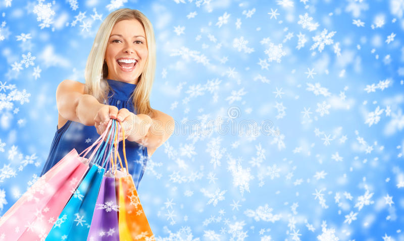 Christmas shopping. Smiling woman . Over snow background royalty free stock photography