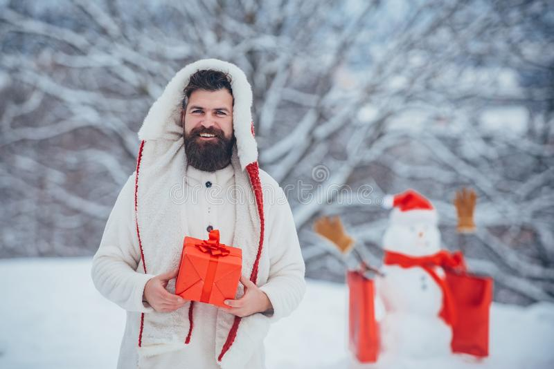 Christmas shopping with shopping bag. Christmas sale and discounts. Handsome Winter Man with gift and snowman in frosty stock image