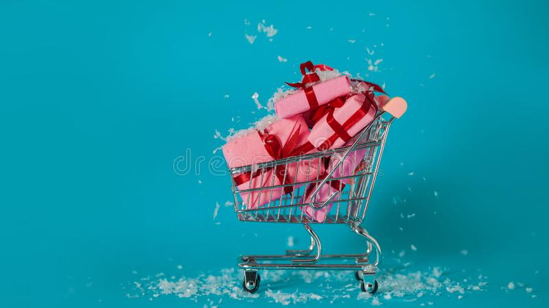 Christmas shopping. Buying gifts for the new year, the concept. The shopping cart is full of gift boxes. Snowflakes fall on pink gift boxes royalty free stock images