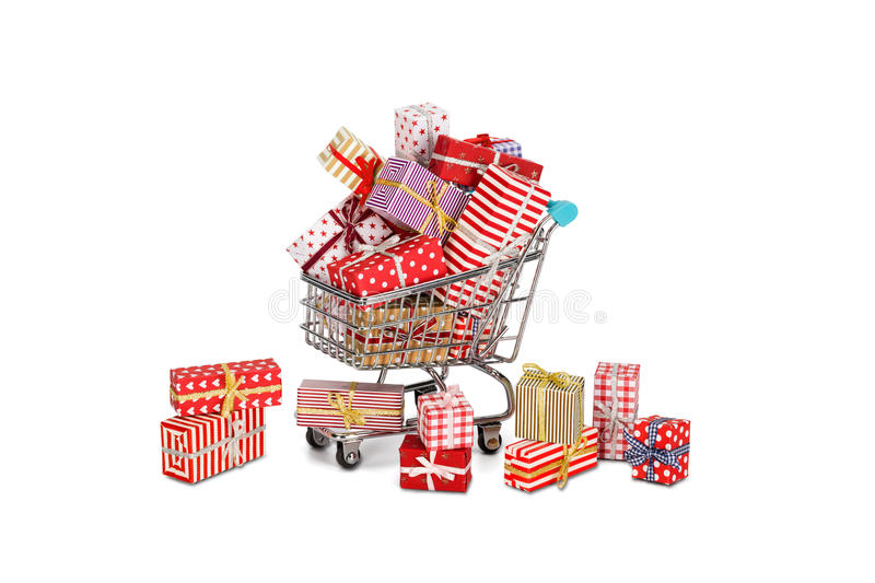 Christmas shopping. Shopping cart filled with christmas gifts with some fallen outside. Christmas shopping theme royalty free stock image