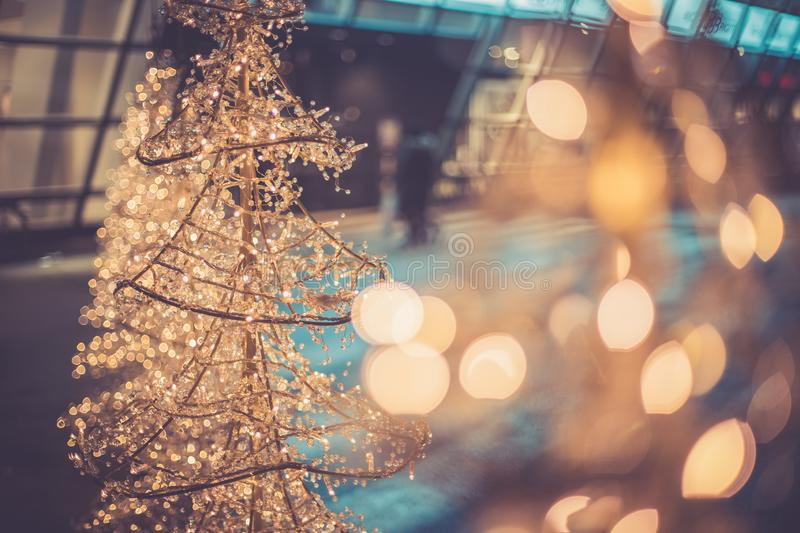 Christmas shopping: christmas lighting in front of a shopping mall. Close up of Christmas decoration lighting in front of a shopping mall, defocused, market stock photo