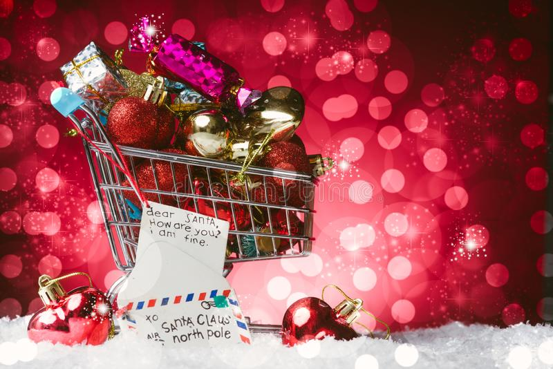 Christmas Shopping concept, a cart full of gift and a letter to santa claus decoration, on snow, against a gorgeous red. Bokelicious background royalty free stock images