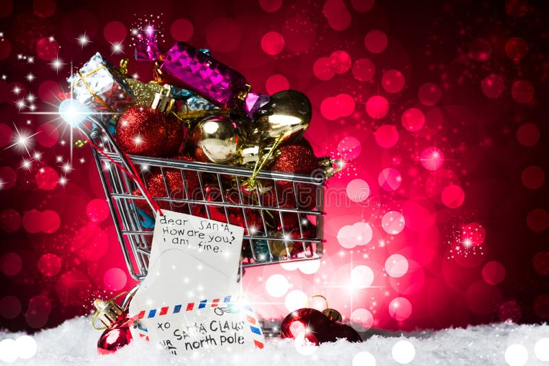 Christmas Shopping concept, a cart full of heart. Decortion red, a on snow, against a gorgeous yellow bokelicious background stock photos