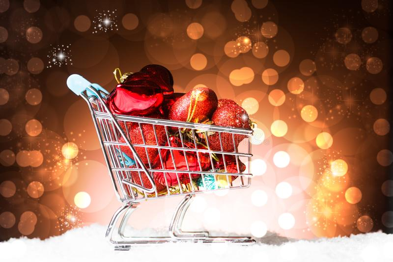Christmas Shopping concept, a cart full of heart. Decortion red, a on snow, against a gorgeous yellow bokelicious background stock photo