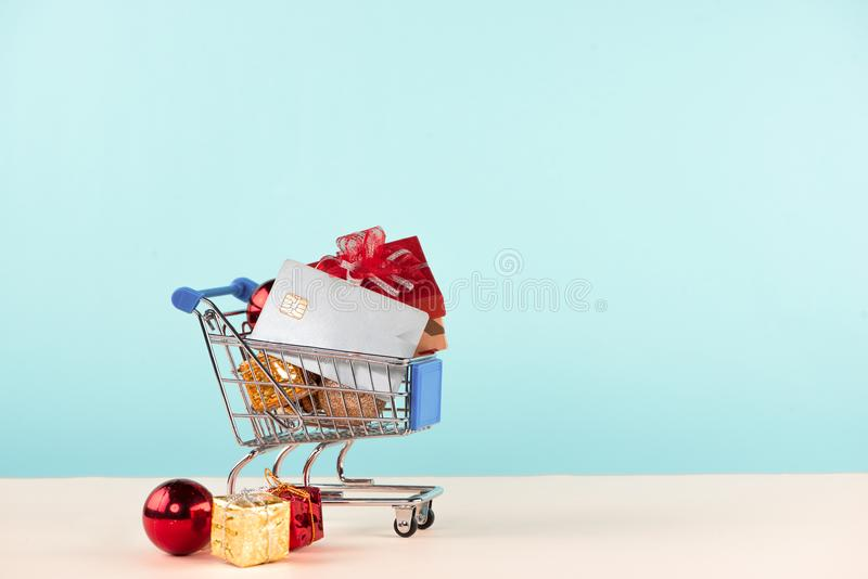 Christmas shopping concept. Shopping cart full with christmas gi. Ft boxes and credit card stock images