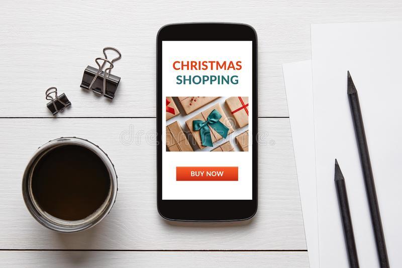 Christmas shopping concept on smart phone screen. With office objects on white wooden table. Top view royalty free stock images
