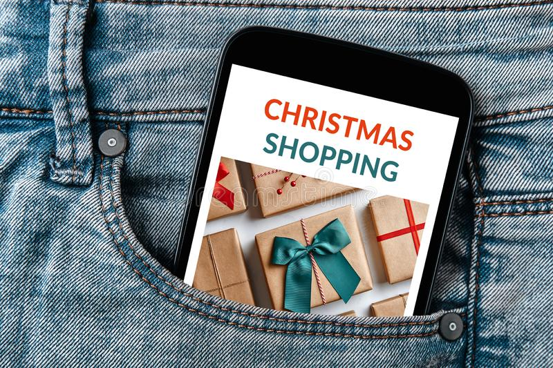 Christmas shopping concept on smartphone screen. In jeans pocket royalty free stock photo