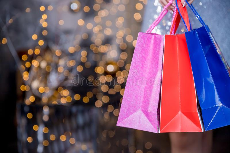 Christmas Shopping. Elegant woman in silver dress In Shopping Mall. Shopping Bags. Holidays and New Year Sales.Woman royalty free stock photography