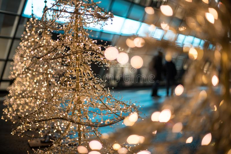 Christmas shopping: christmas lighting in front of a shopping mall. Close up of Christmas decoration lighting in front of a shopping mall, defocused, market royalty free stock photo