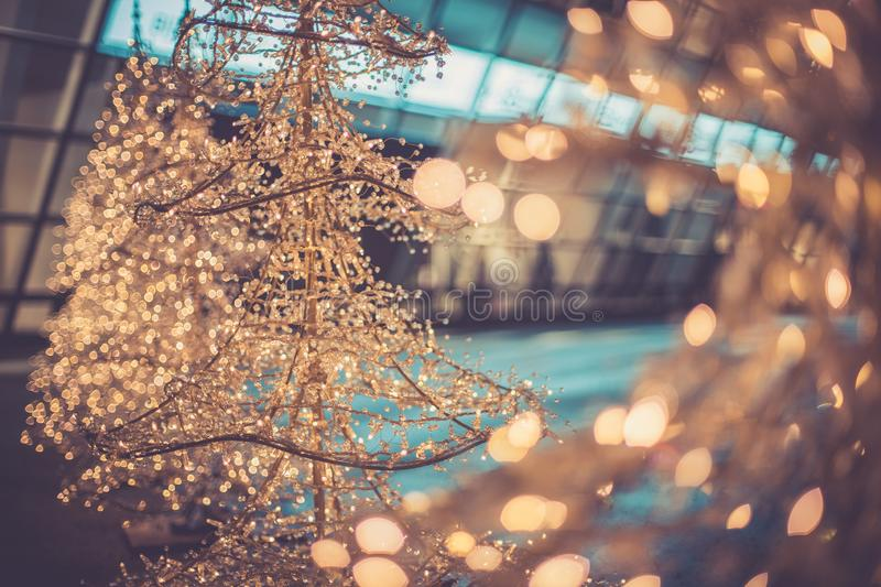 Christmas shopping: christmas lighting in front of a shopping mall. Close up of Christmas decoration lighting in front of a shopping mall, defocused, market stock image