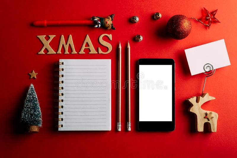 Christmas shopping list and mobile phone, Holiday planning red background, notebook and christmas decoration stock photography