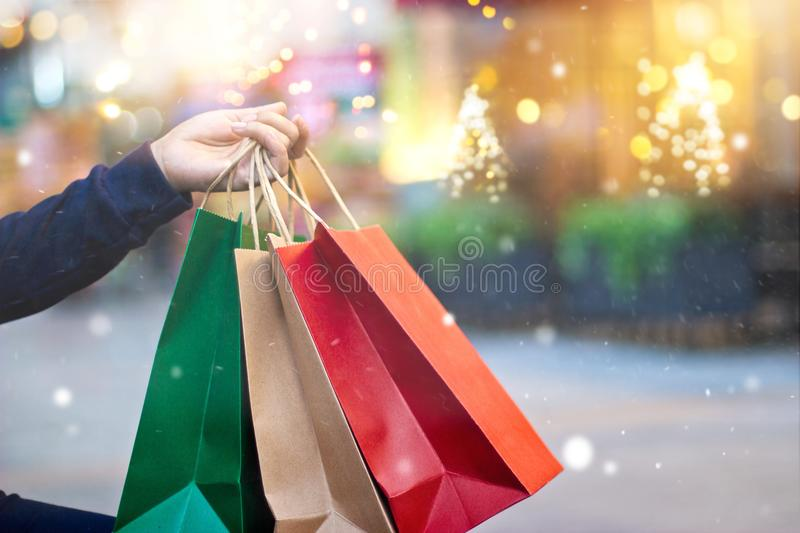 Christmas shopping-shopping bags in hand with snowflake. Christmas shopping - shopping bags in hand with snowflake on christmas decoration and lighting on street royalty free stock photo