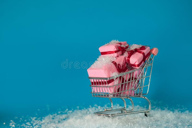 Christmas shopping on site. Buying gifts for the new year, the concept. The shopping cart is full of gift boxes. Snowflakes fall on the purchase stock images