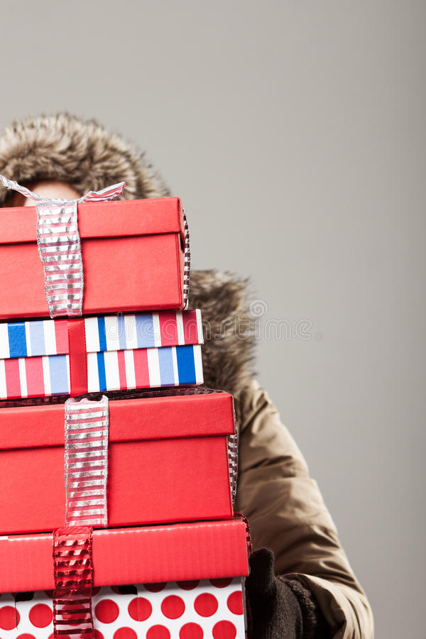 Christmas shopping stress. A woman in a winter anorak is hidden behind a tall stack of colourful decorative Christmas presents as she returns from a day out royalty free stock image