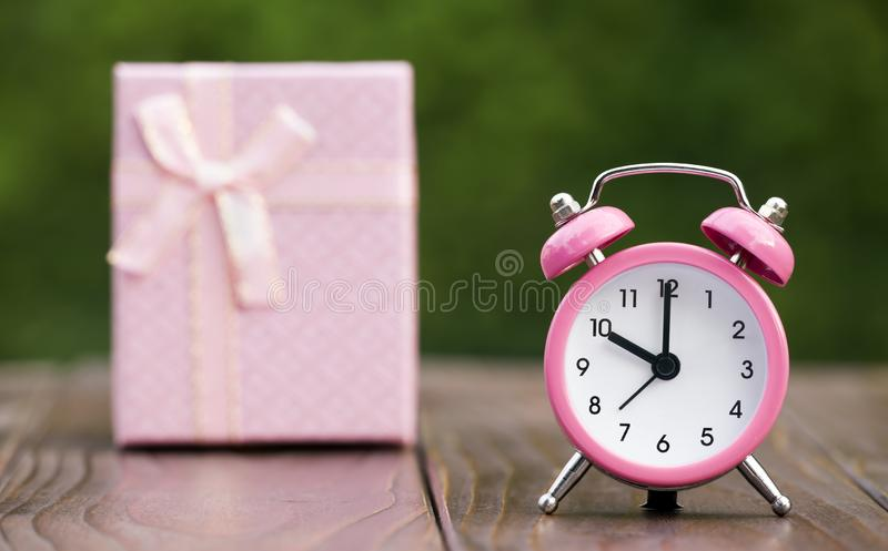 Christmas shopping, time to gift. Pink alarm clock and gift box royalty free stock photo