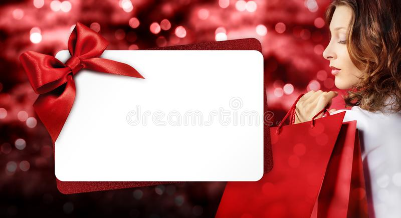 Christmas shopping, woman with bag and gift card template on blu. Rred bright lights background, banner template with copy space stock photo