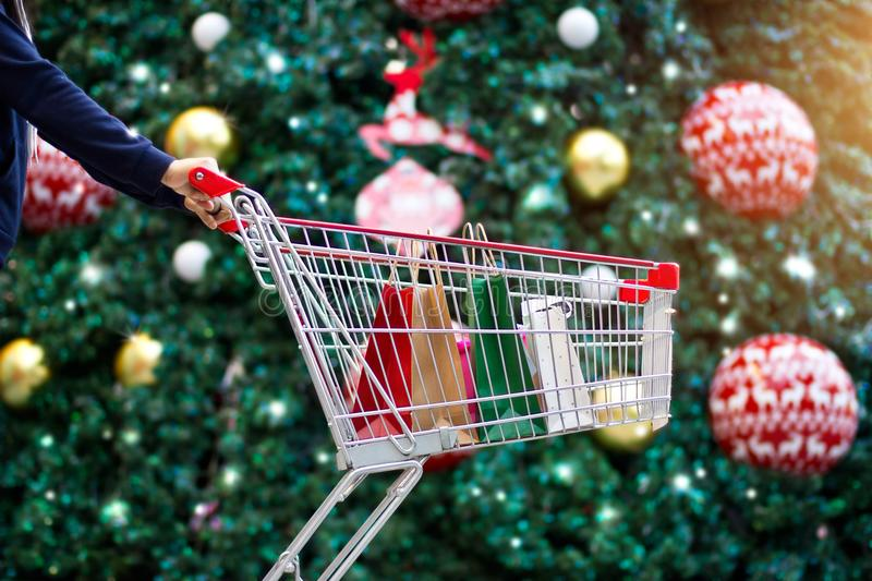 Christmas shopping-woman shopper,shopping bags in cart stock images