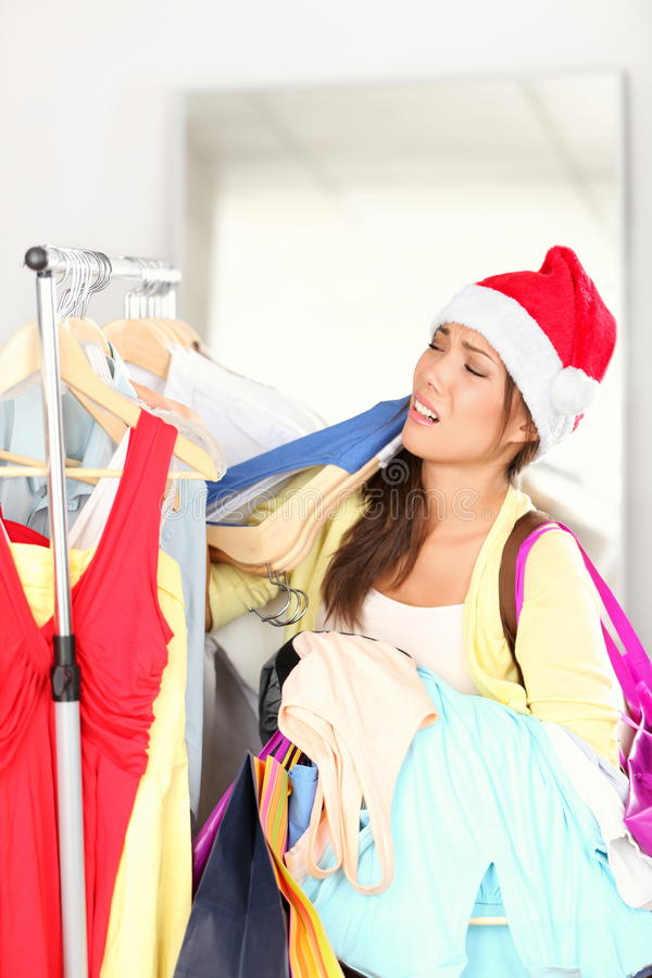 Christmas shopping - woman tired. Funny image of woman exhausted from Christmas sales. Young Asian woman wearing Santa hat stock photo