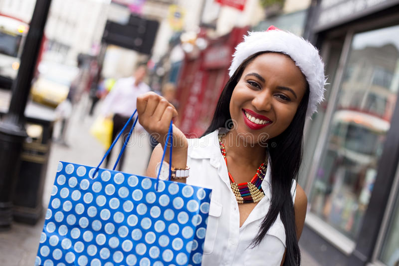 Christmas shopping. Young woman wearing a christmas hat holding a shopping bag royalty free stock images