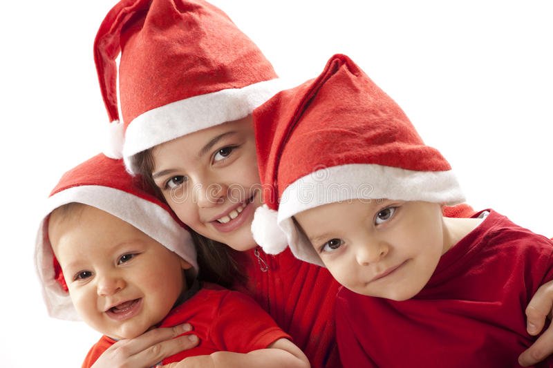 Christmas siblings. Portrtait of a girl and two boys in christmas hats royalty free stock photo