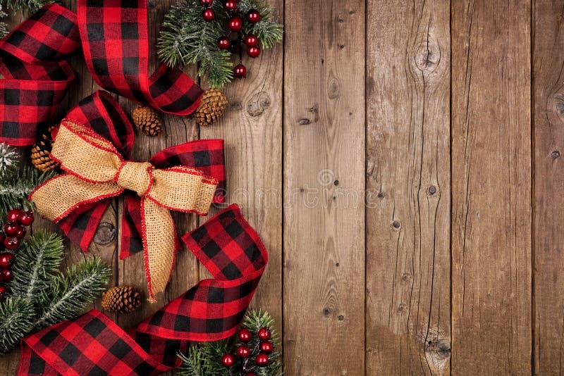 christmas side border red black checked buffalo plaid ribbon burlap tree branches overhead view rustic wood 163887919