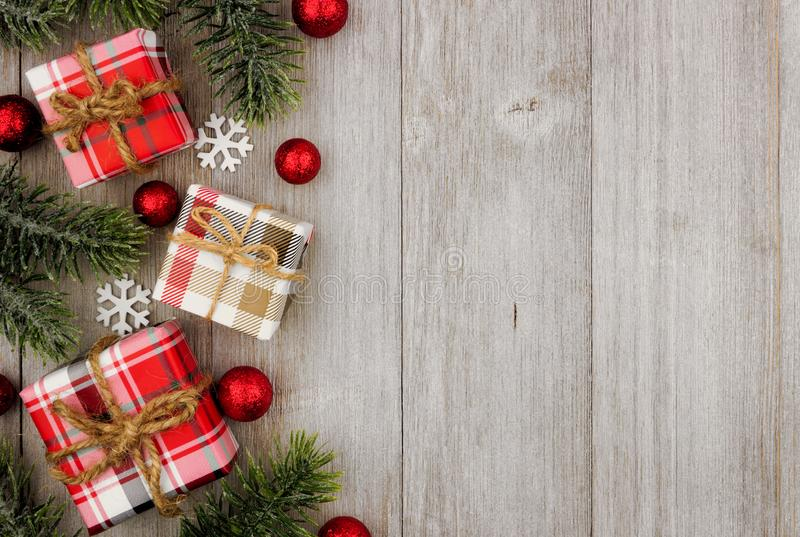 Christmas side border gifts and tree branches on gray wood stock image
