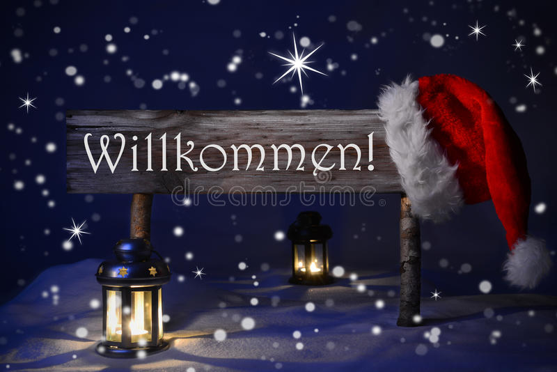 Christmas Sign Candlelight Santa Hat Willkommen Means Welcome. Wooden Christmas Sign And Santa Hat With Snow Snowy Scenery. German Text Willkommen Means Welcome stock image