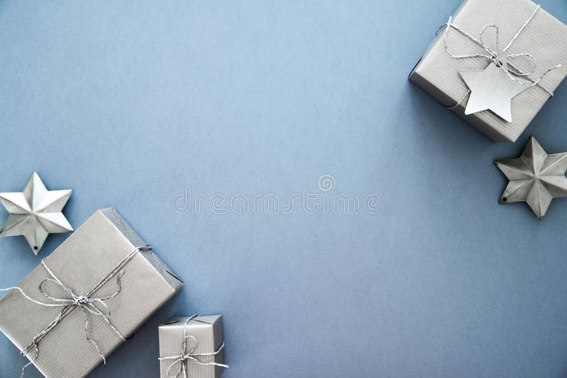 Christmas silver handmade gift boxes on blue background top view. Merry Christmas greeting card, frame. Winter xmas holiday theme. royalty free stock photography