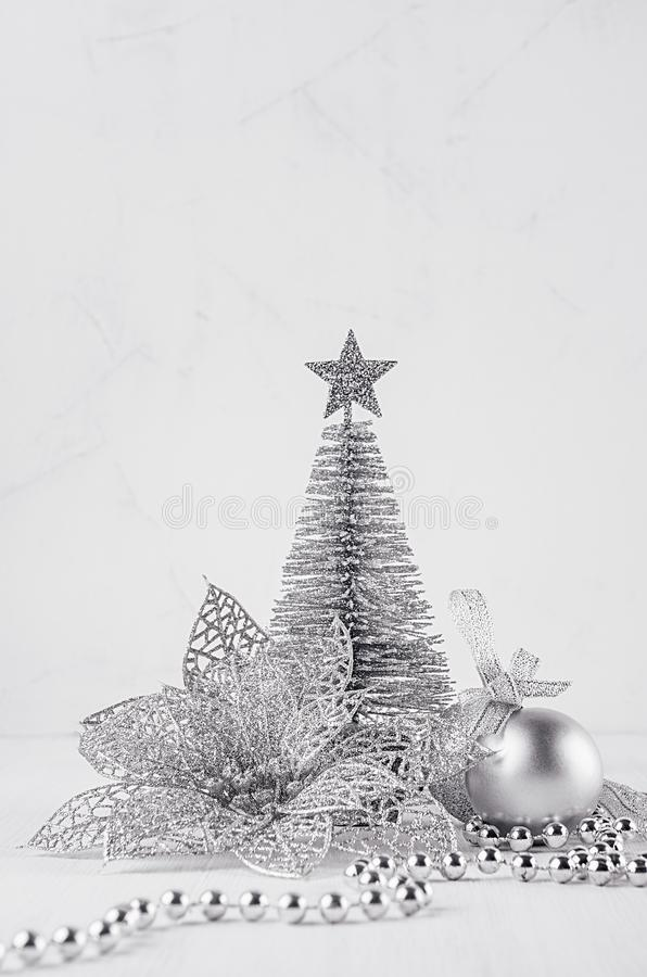 Christmas silver tree and decorations on white soft wood background. Festive interior. Christmas silver tree and decorations on white soft wood background stock photo
