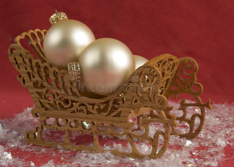 Christmas Sleigh. Wooden Christmas sleigh with ivory and gold bulb ornaments on a red background with snowflakes royalty free stock images