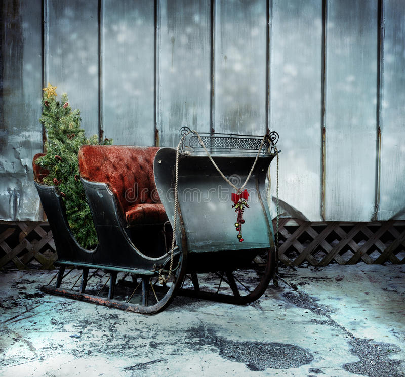 Christmas sleigh. An antique Santa's sleigh with decorations and a Christmas tree in the back seat. Concept for a past season of Christmas stock image