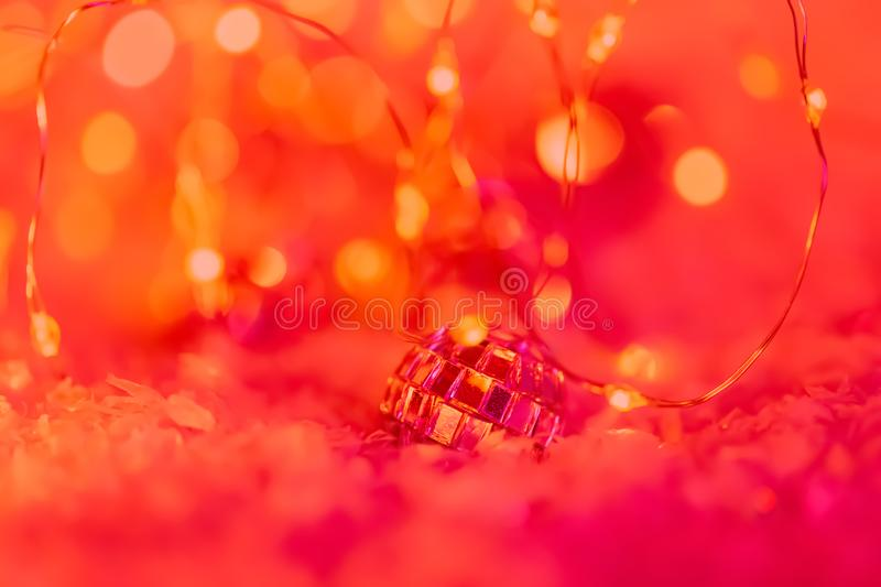 Christmas. Small decorative ball with a mirror and a glittering garland on a snow. Blurred festive red background with bokeh. royalty free stock image