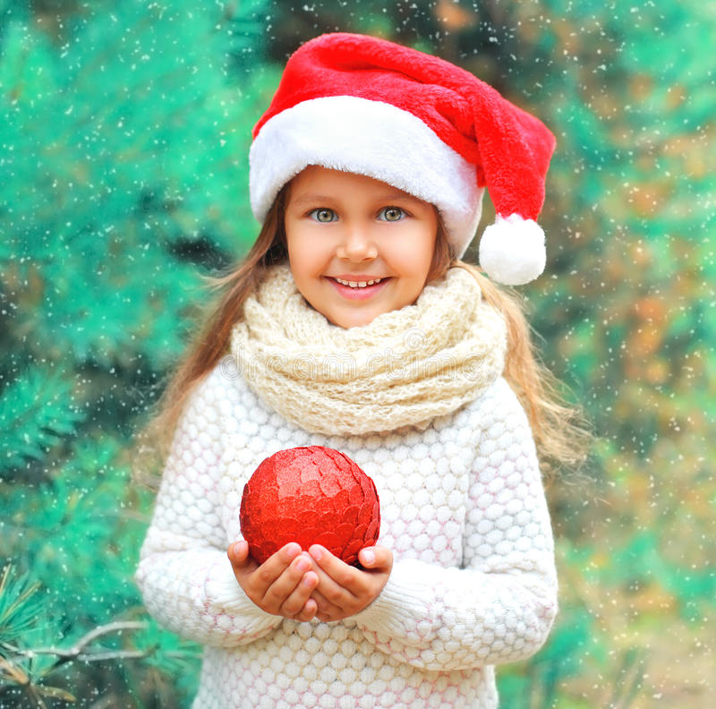 Free Christmas Smiling Child Little Girl In Santa Red Hat With Ball Near Tree Stock Image - 81010411