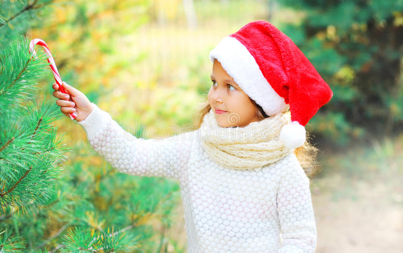 Christmas smiling child little girl in santa red hat decoration, sweet lollipop cane to branch tree stock photos