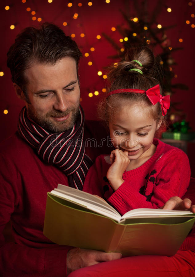 Christmas - smiling father and daughter reading a book. Christmas eve - happy family time. Smiling father and daughter read book on dark red background with royalty free stock images