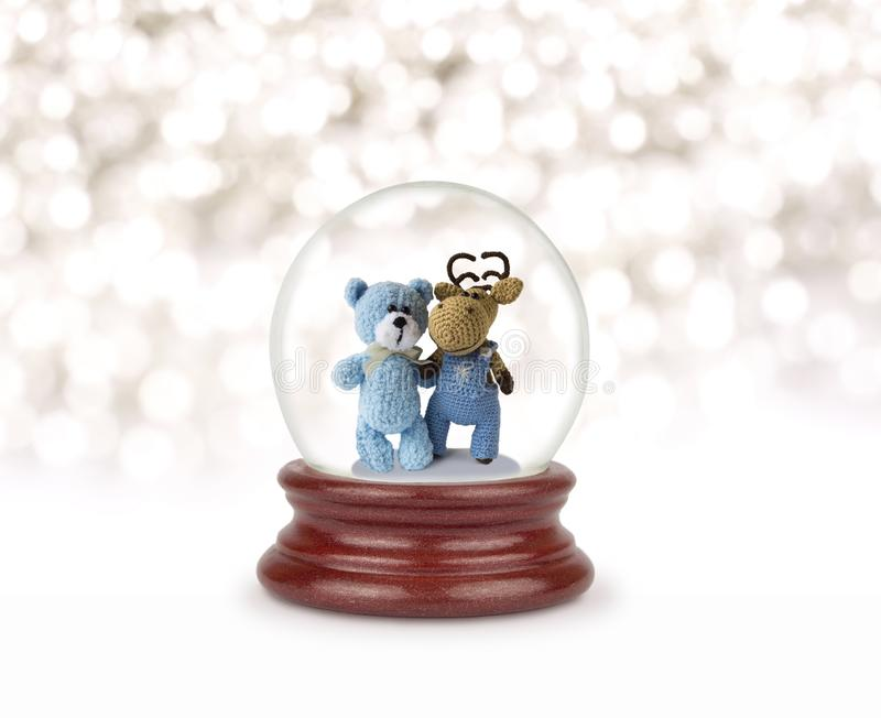Christmas snow. Can be used as a Christmas or a New Year gift or symbol. Christmas and New Year design element. Toy glass snow globe with teddy bear and deer stock photo