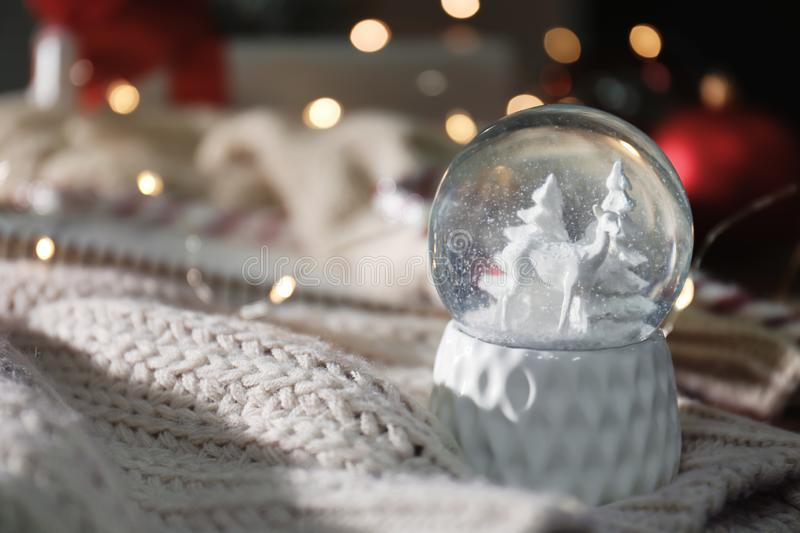Christmas snow globe with knitting clothes on blurred background. Space for text stock photo