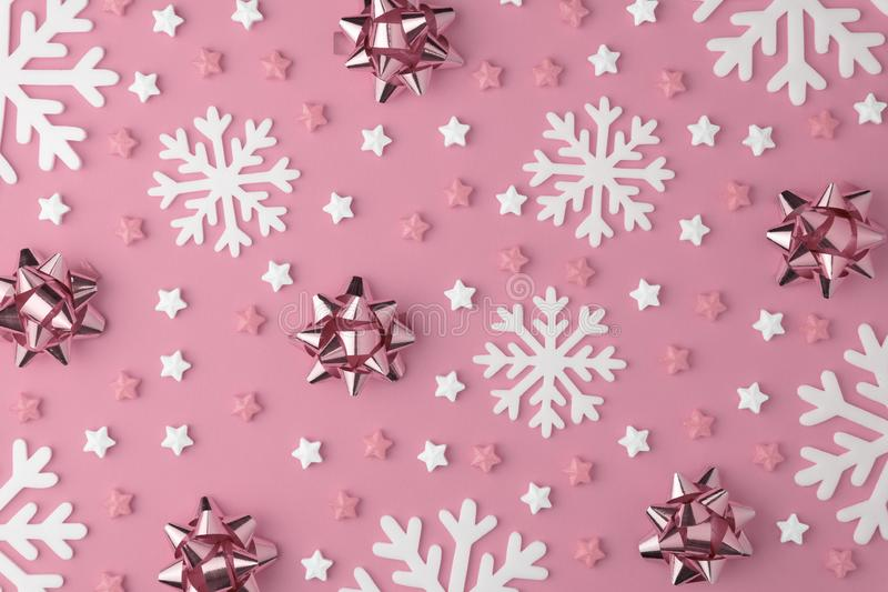 Christmas snowflake pattern with Lollipops and sweets Candy flat lay on pink pastel background. Minimal concept stock image