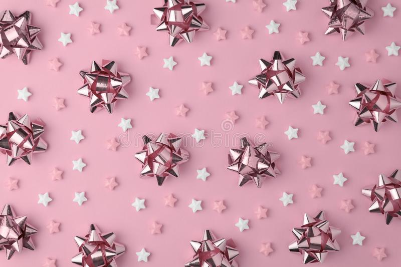 Christmas snowflake pattern with Lollipops and sweets Candy flat lay on pink pastel background. Minimal concept royalty free stock photos